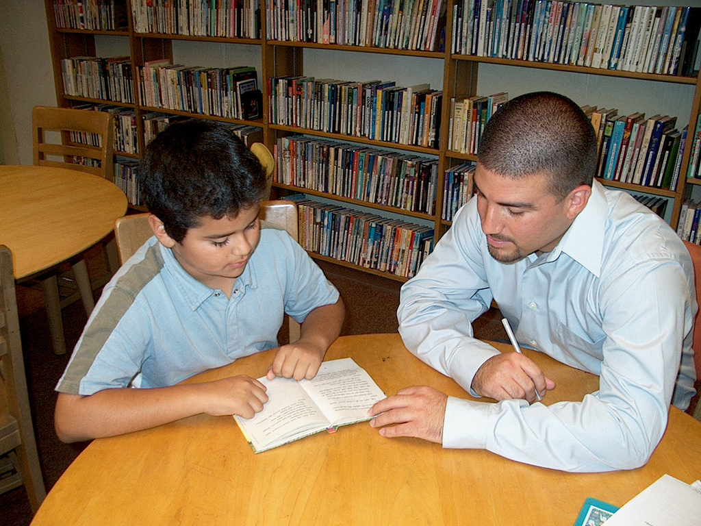 Child and a tutor reading a book