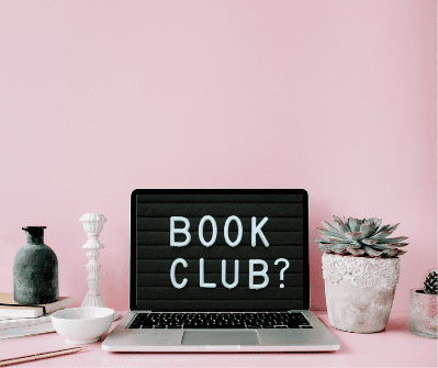 Words book club? on a laptop screen with a candlestick, vase and plant