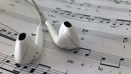 photograph of a pair of apple ear buds laying on top of classical sheet music
