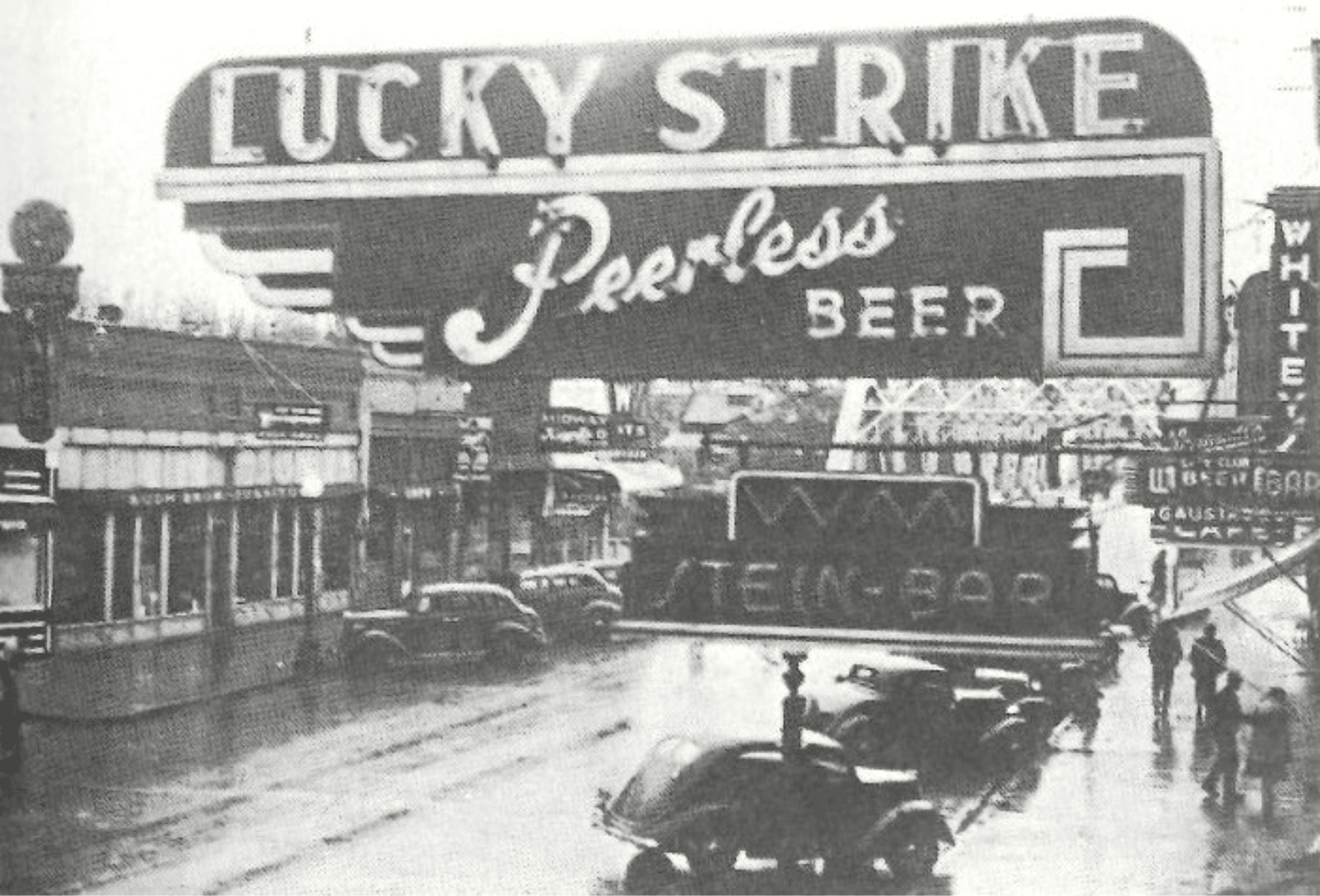 Demers Ave circa 1938 featuring neon signs for Luck Strike Peerless Beer, Wonderbar, and W M Stiens